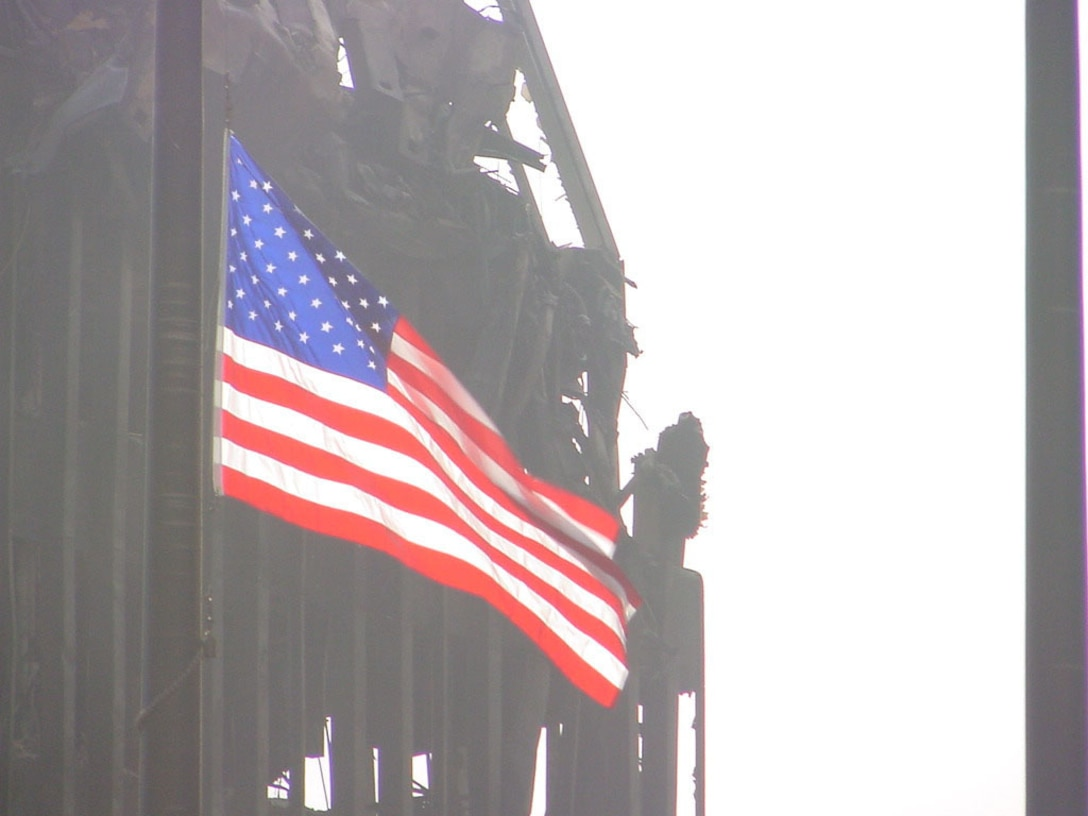 NEW YORK -- The United States flag is cast against a backdrop of destruction caused by the attack on the Twin Towers of the National World Trade Center here Sept. 11.  Air Force airmen joined other workers in helping to clear the rubble and search for survivors.  (U.S. Air Force photo by Capt. Jim Fabio)
