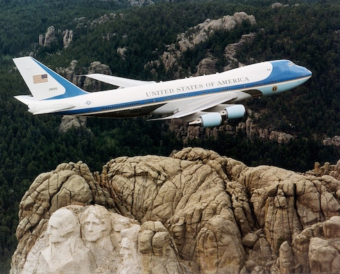 FILE PHOTO -- Air Force One flies over Mount Rushmore. Principal differences between the VC-25A and the standard Boeing 747, other than the number of passengers carried, are the electronic and communications equipment aboard Air Force One, its interior configuration and furnishings, self-contained baggage loader, front and aft air-stairs, and the capability for in-flight refueling. These aircraft are flown by the presidential aircrew, maintained by the presidential maintenance branch, and are assigned to Air Mobility Command's 89th Airlift Wing, Andrews Air Force Base, Md. (U.S. Air Force photo)