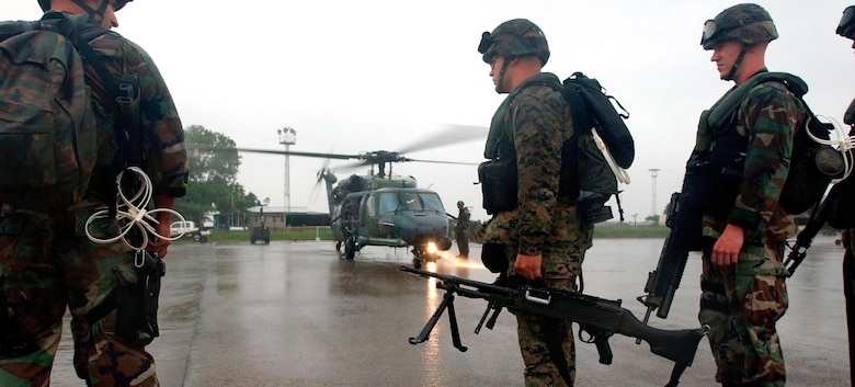 LUNGI, Sierra Leone -- Marines prepare to board an Air Force HH-60G Pave Hawk helicopter here July 21.  The Marines are part of an antiterrorism security team augmenting security at the U.S. Embassy in Monrovia, Liberia.  The helicopters are deployed form Naval Air Station Keflavik, Iceland, as part of the 398th Air Expeditionary Group.  The group provides recovery and emergency evacuation capabilities in Liberia.  (U.S. Air Force photo by Tech. Sgt. Justin D. Pyle)
