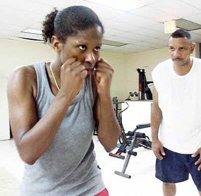 EGLIN AIR FORCE BASE, Fla. -- Staff Sgt. Charmaine Carrington takes pointers from her coach, Dennis Walker.  Carrington is the first female on the Air Force boxing team.  She will box in her first national match June 18.  Carrington is a weapons-load crew chief assigned to the 33rd Aircraft Maintenance Squadron here.  (U.S. Air Force photo by Staff Sgt. Jerron Barnett)