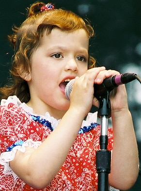 """AGAWAM, Mass. -- Six-year-old Jordyn Tabury set the stage for country-music artist Lee Greenwood at a military appreciation day concert at Six Flags in Agawam, Mass., on June 14.  Jordyn opened the concert when she sang Greenwood's """"God Bless the USA"""" song for more than 1,000 people at the concert.  She is the daughter of Staff Sgt. Peter and Bernadette Tabury from the 319th Recruiting Squadron in Bristol, Conn.  (U.S. Air Force photo by Staff Sgt. Michael O'Connor)"""
