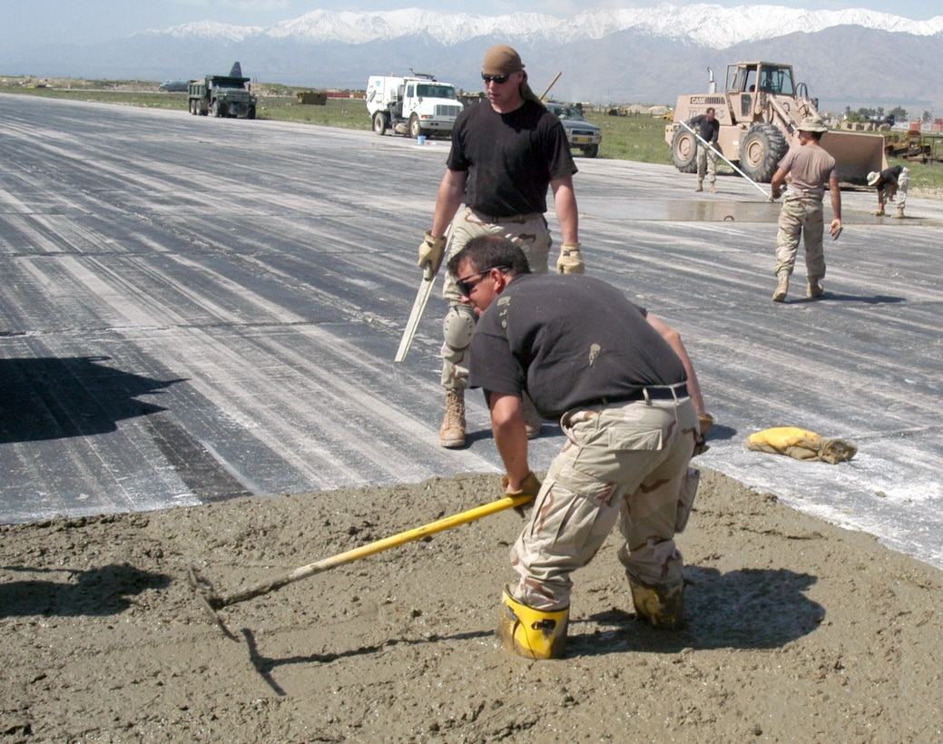 OPERATION ENDURING FREEDOM (AFPN) -- Tech. Sgt. James Holman spreads concrete in a hole on the active runway at Bagram Air Base, Afghanistan, as part of a $2.3 million airfield repair project.  Holman is deployed form the 48th Civil Engineer Squadron at Royal Air Force Lakenheath, England.  (U.S. Air Force photo by Tech. Sgt. Adam Johnston)