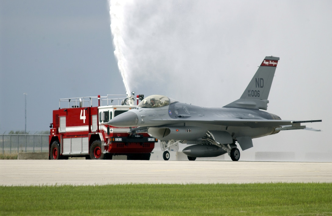 FARGO, N.D. (AFPN) -- Lt. Col. Dana S. Mullenhour steers aircraft No. 82-1006, through a shower here May 14 to celebrate the completion of 60,000 accident-free flying hours in the F-16 Fighting Falcon for the 119th Fighter Wing.  Overall, the North Dakota Air National Guard has amassed more than 132,400 flying hours without a Class A mishap.  (U.S. Air Force photo by Senior Master Sgt. David H. Lipp)