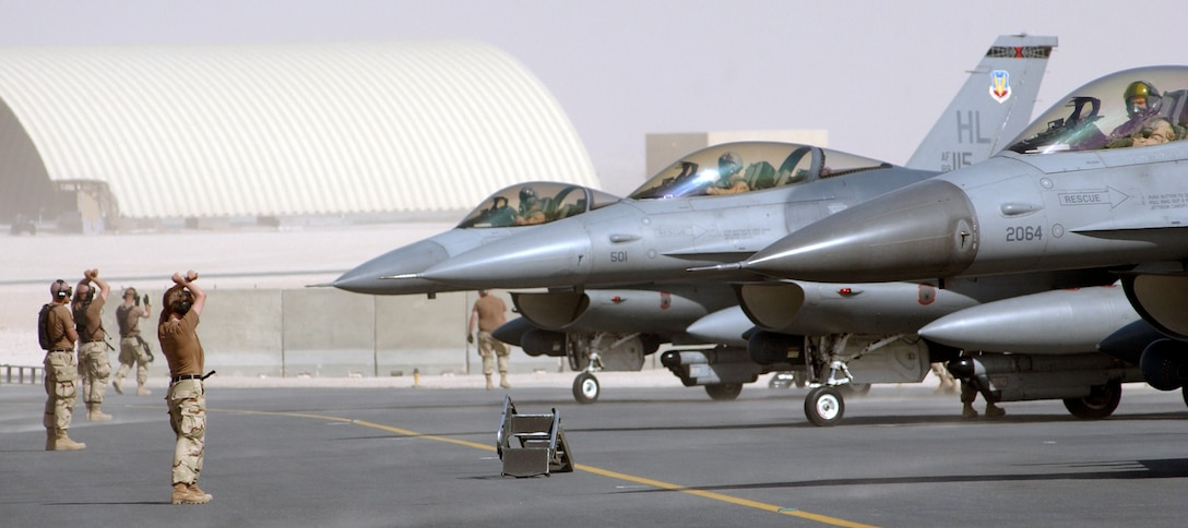 OPERATION IRAQI FREEDOM -- Crew chiefs marshal F-16 Fighting Falcons toward parking spots at a forward-deployed location in Southwest Asia.  Airmen and aircraft from Hill Air Force Base, Utah, are currently deployed supporting Operation Iraqi Freedom.  (U.S. Air Force photo by Master Sgt. Terry L. Blevins)