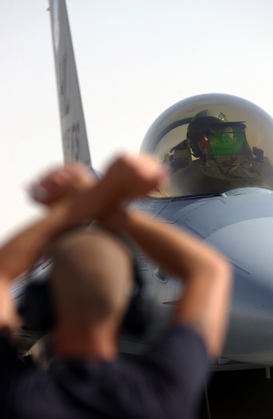 OPERATION IRAQI FREEDOM -- A crew chief signals a pilot to park his F-16 Fighting Falcon at a forward-deployed location in Southwest Asia.  Airmen and aircraft from Hill Air Force Base, Utah, are currently deployed supporting Operation Iraqi Freedom.  (U.S. Air Force photo by Master Sgt. Terry L. Blevins)