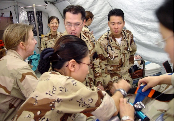 MANAS AIR BASE, Kyrgyzstan -- Members of the 376th Expeditionary Medical Group and South Korea's 924th Medical Group work together on a simulated patient during an exercise at the hospital here.  (South Korean army photo by Cpl. Hongyeon Kim)
