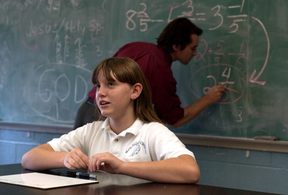 FAIRBORN, Ohio -- Killie Rick explains her new method of solving subtraction of fractions problems, as her teacher, Colin McCabe, puts an example on the chalkboard.  She uses negative numbers, which McCabe said he had never seen before.  Killie is a seventh-grade student at Mary Help of Christians school here.  Her mother is Terri Rick, an employee at nearby Wright-Patterson Air Force Base.  (U.S. Air Force photo by Spencer P. Lane)