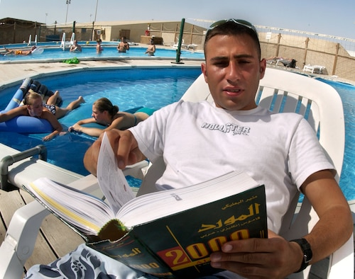 SOUTHWEST ASIA -- Airman 1st Class Ramin Amely sits poolside and reads a Farsi-English dictionary at an undisclosed desert location.  He is assigned to the 380th Expeditionary Security Forces Squadron.  His language skills help his unit work with host-nation patrols to guard the base.  (U.S. Air Force photo by Master Sgt. Lance Cheung)