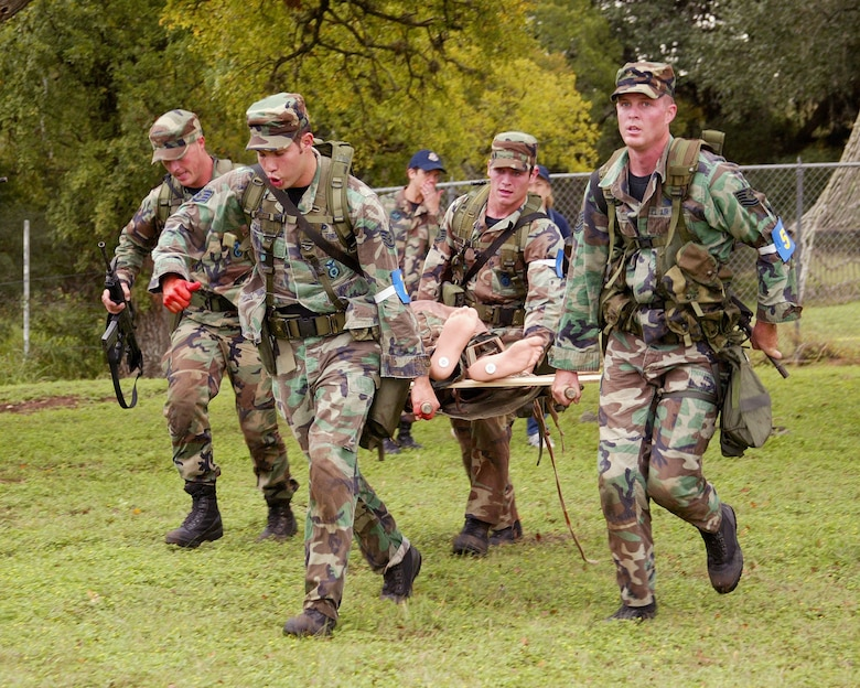 "CAMP BULLIS, Texas -- Defender Challenge competitors from the Air Education and Training Command team move a ""battlefield casualty"" mannequin to the evacuation staging area.  The action took place during the Warrior Challenge event, which the AETC team won.  Team members pictured are (left to right) 2nd Lt. Matt Gravelink from the 56th Security Forces Squadron at Luke Air Force Base, Ariz.; Staff Sgts. Marco Talamantez and Vance Smith from the 37th SFS at Lackland AFB, Texas; and Tech. Sgt. Danile Hoyme from the 342nd Training Squadron at Lackland.  (U.S. Air Force photo by Robbin Cresswell)"