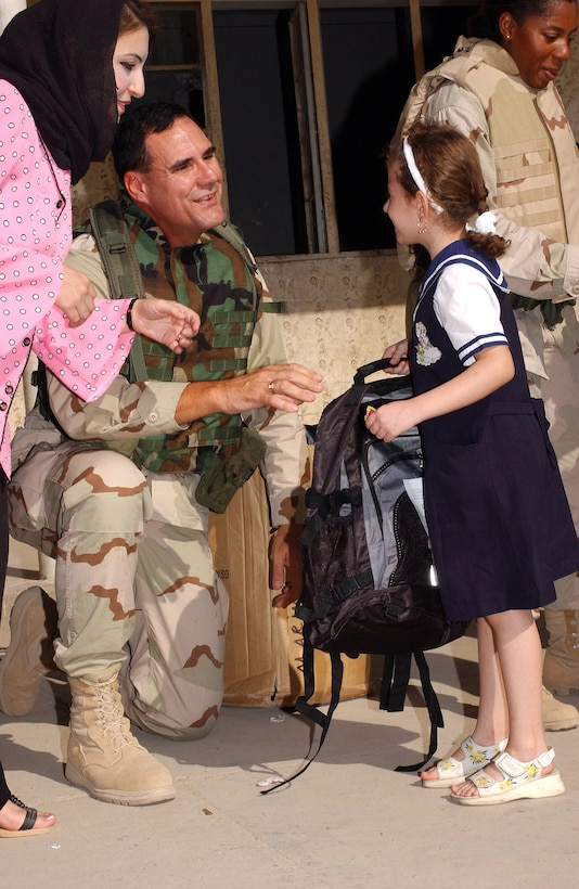 KIRKUK, Iraq -- Col. Steven Johnson passes out school supplies to children at a school here Oct. 22.  Airmen from the 380th Air Expeditionary Wing traveled from a forward-deployed air base to donate more than $5,000 of supplies to schools here.  Johnson is the commander of the 380th Expeditionary Mission Support Group.  (U.S. Air Force photo by Staff Sgt. James A. Williams)