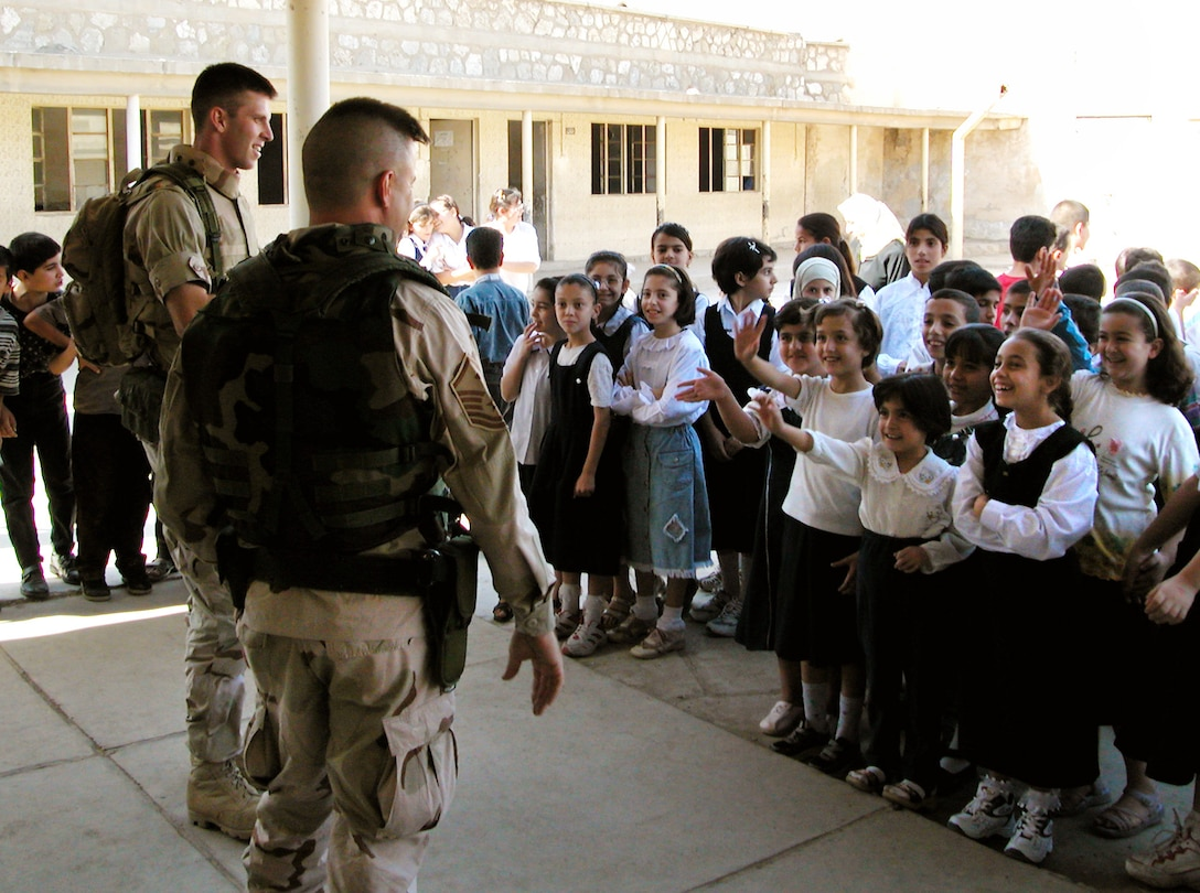 KIRKUK, Iraq -- Master Sgt. Robert Frank and 1st Lt. Art Patek talk with students at Al Ilaf school here.  The two were part of a team from the 380th Air Expeditionary Wing who traveled from a forward-deployed air base to donate more than $5,000 of supplies to schools here.  Frank is the first sergeant of the 380th Expeditionary Mission Support Group, and Patek is the 380th Expeditionary Operations Group executive officer.  (U.S. Air Force photo by Maj. Robert Couse-Baker)