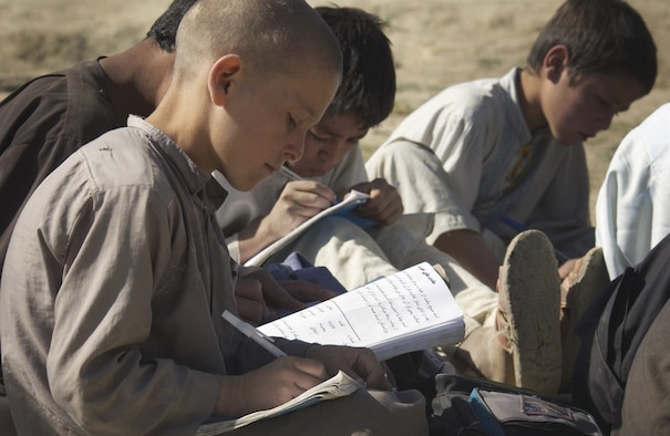 BAGRAM, Afghanistan -- Afghan boys study writing at an outdoor school.  Whenever the winds blow, or it rains, school is cancelled.  On Oct. 19, airmen delivered an old eight-section tent that will serve as a new school for the children.  (U.S. Air Force photo by Master Sgt. Lance Cheung)