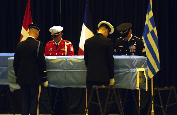 YOKOTA AIR BASE, Japan -- Members of the U.N. Honor Guard pay their final respect to remains believed to be those of U.S. soldiers during a repatriation ceremony here Oct. 28.  Eight caskets, each draped in a pale blue U.N. flag, were carried by military honor guards into a hangar after being flown in from North Korea.  (U.S. Air Force photo by Master Sgt. Val Gempis)