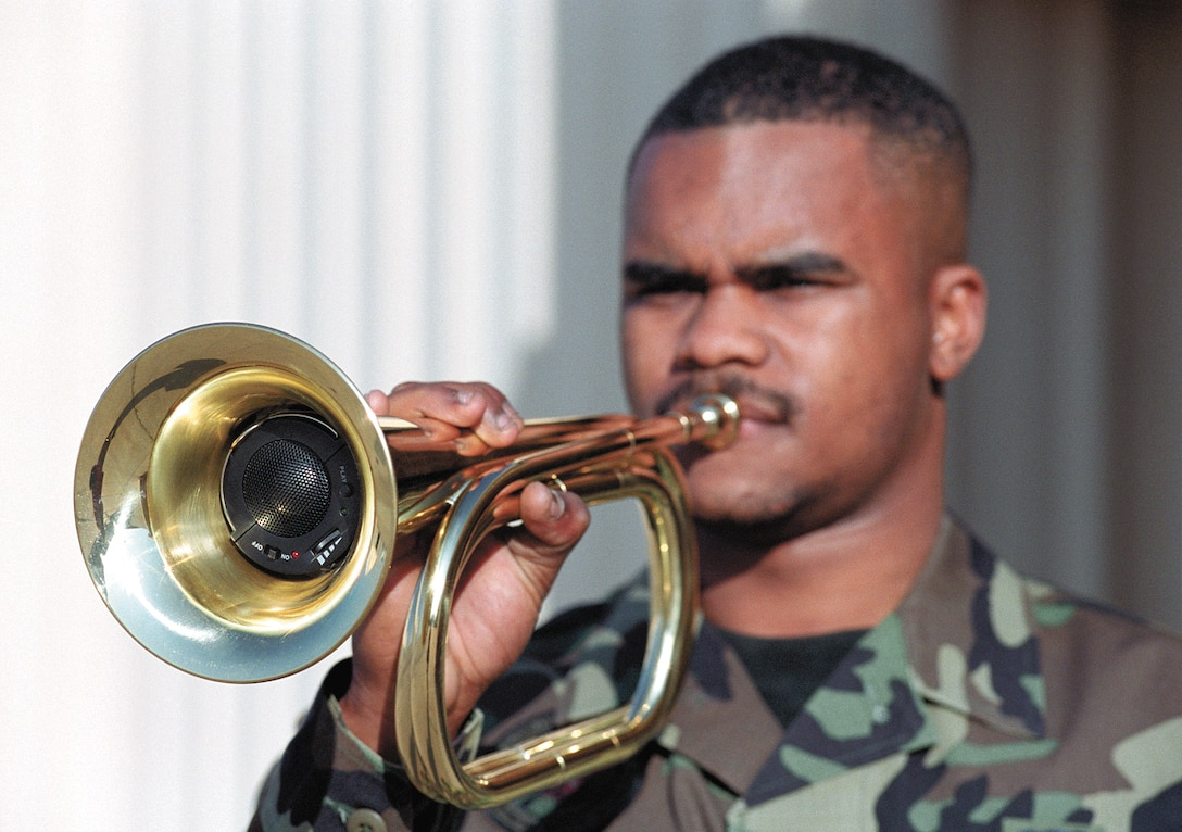 """TINKER AIR FORCE BASE, Okla. -- A recorder that plays """"Taps"""" tucks inside a special bugle held by Senior Airman Eric Young.  Tinker Air Force Base Honor Guard members said they welcome the bugles over the stereos they had to use in the past.  Airman Young is an honor guard supply technician and bugler.  (U.S. Air Force photo by Margo Wright)"""