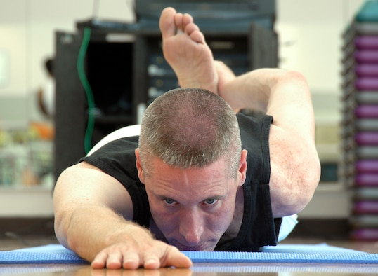 LOS ANGELES AIR FORCE BASE, Calif. -- Capt. William Uhl holds a half-frog asana, or pose, during the cool-down phase of his hour-long yoga class in the fitness center here.  He has been practicing yoga for four years and is certified to teach yoga, Pilates and Power Stretch, which combines yoga and Pilates.  The captain is an analyst for the Space and Missile Systems Center's intelligence directorate. (U.S. Air Force photo by Jason M. Webb)