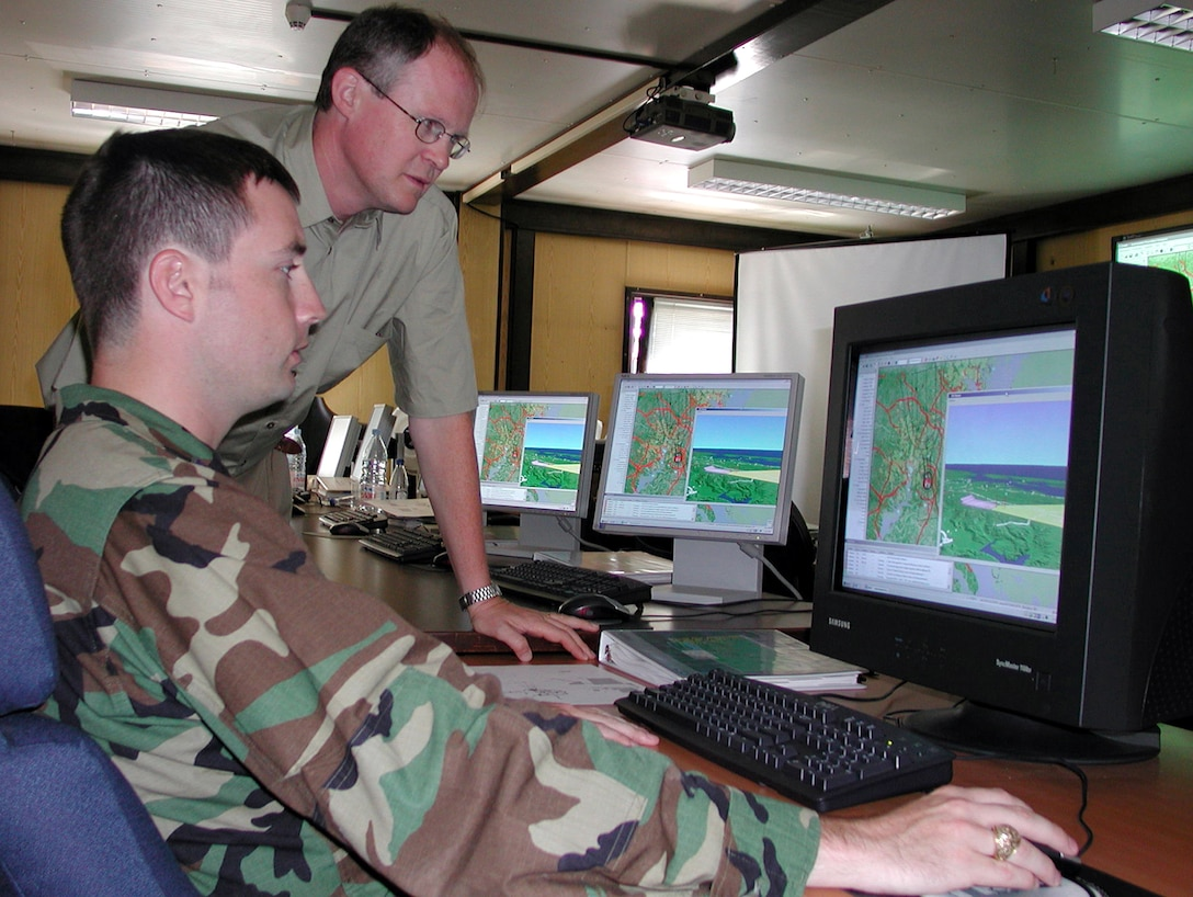 RAMSTEIN AIR BASE, Germany -- Capt. Mack Coker (foreground) learns how to use the Global Procedure Designer with the help of Iain Hammond, a systems engineer for MacDonald Dettwiler.  The GPD is a new software-based program providing terminal instrument procedures specialists with a better evaluation of obstacles and terrain in the arrival and departure path for aircraft.  Captain Coker is the air procedures flight commander for U.S. Air Forces in Europe.  (U.S. Air Force photo by Tech. Sgt. Mona Ferrell)