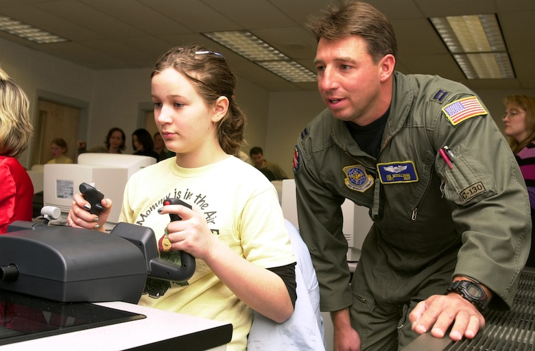MARTINSBURG, W.Va. (AFPN) -- Fifth-grader Catherine Newcome, at the yoke, gets a feel for flying a small plane on a computer simulator during a National Guard Starbase exercise in Martinsburg, W.Va. Capt. Jon McCullough, a C-130 Hercules pilot in the West Virginia Air National Guard, offers some helpful hints while watching her progress. (U.S. Air Force photo by Master Sgt. Bob Haskell)