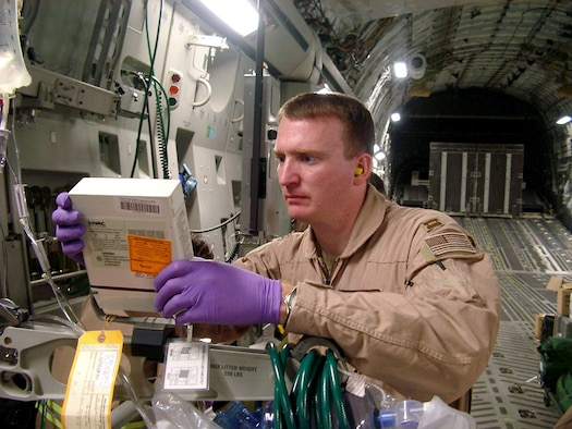 OPERATION SOUTHERN WATCH -- Capt. Paul Simpson fixes an IV fluid pump aboard an aerovac mission. Besides providing patient care, aeromedical evacuation crews must maintain and operate a variety of medical equipment before and throughout each mission. Simpson is a second flight nurse deployed with the 320th Expeditionary Aeromedical Evacuation Squadron/Forward from the 375th Aeromedical Evacuation Squadron at Scott Air Force Base, Ill. (Courtesy photo)