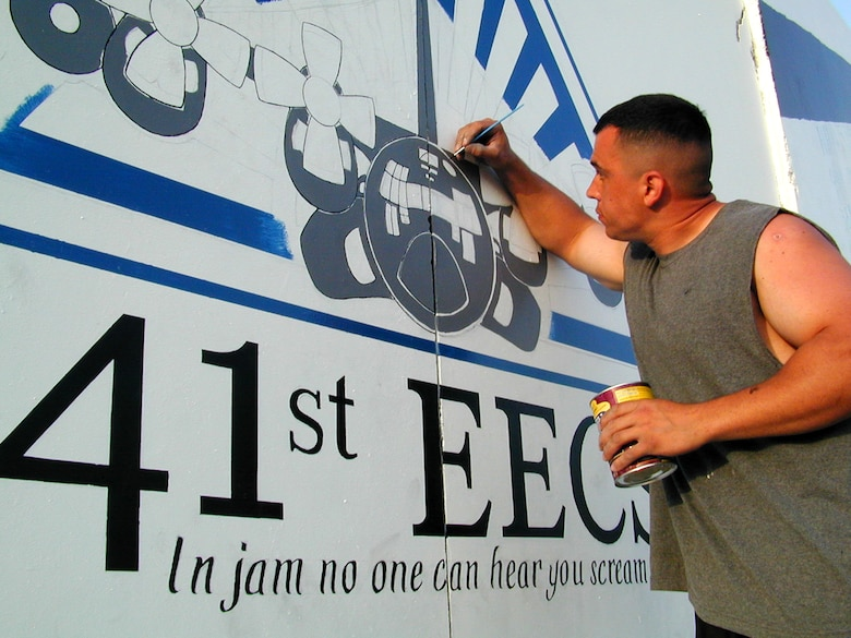 OPERATION ENDURING FREEDOM -- Staff Sgt. John Alsvig touches up his painting of an EC-130H on a mural documenting his unit's arrival on the frontlines of the war on terrorism. Alsvig is a fuels system specialist from the 41st Expeditionary Electronic Combat Squadron.  (U.S. Air Force photo by Master Sgt. Darrell Lewis)