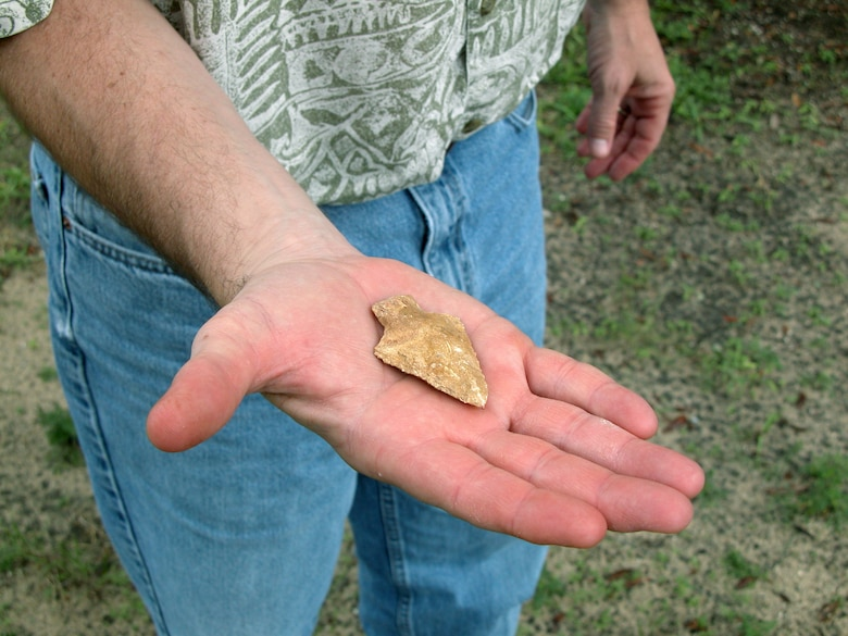 EGLIN AIR FORCE BASE, Eglin -- Mark Stanley displays the American Indian arrowhead found by 6-year-old John David Lilley.  The arrowhead, which dates back to 3,000 to 2,000 B.C., was probably used by descendants of the 18th or 19th century Creeks or Seminoles.  Mr. Stanley is an archaeologist with the environmental program directorate.  (U.S. Air Force photo by Sarah McCaffrey)