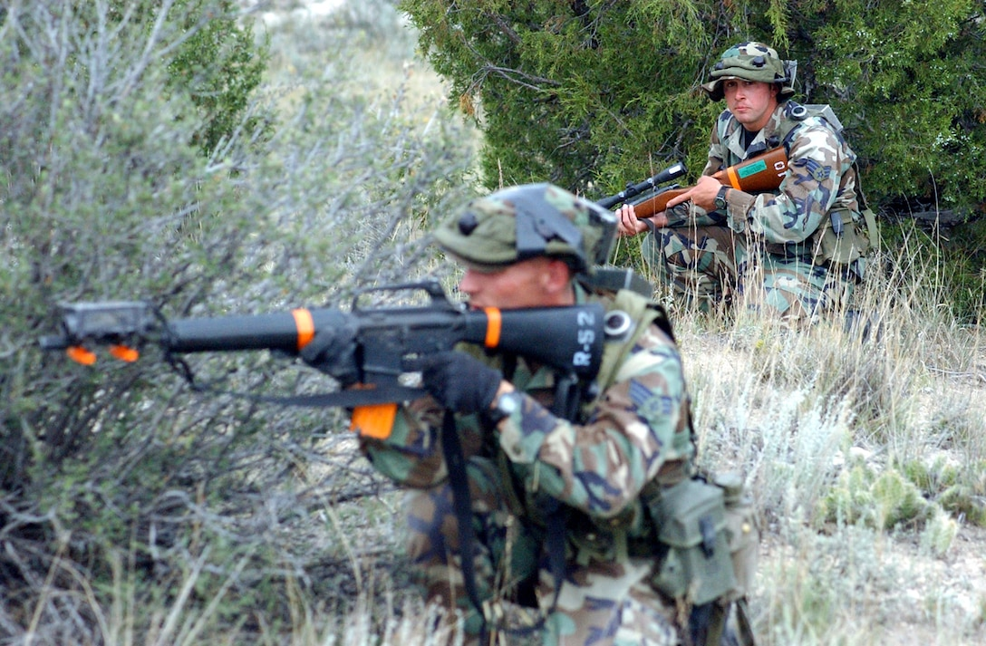 CAMP GUERNSEY, Wyo. -- Senior Airman Matthew James (left) returns fire as Senior Airman Landon Elledge watches his back during the Road Warrior III exercise here.  They are assigned to the 791st Missile Security Forces Squadron at Minot Air Force Base, N.D.  (U.S. Air Force photo by Master Sgt. Jeff Bohn)