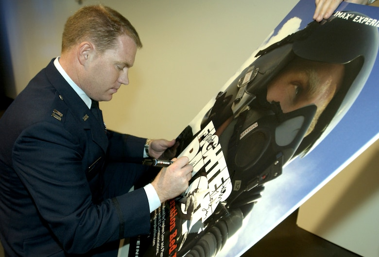 """CHANTILLY, Va. -- Capt. John Stratton signs a movie poster at the premier of the new IMAX film """"Fighter Pilot: Operation Red Flag.""""  He served as the star of the film.  The movie chronicles his experience as he participates in his first Red Flag exercise.  The film made its premier Dec. 2 at the National Air and Space Museum here.  (U.S. Air Force photo by Master Sgt. James Varhegyi)"""