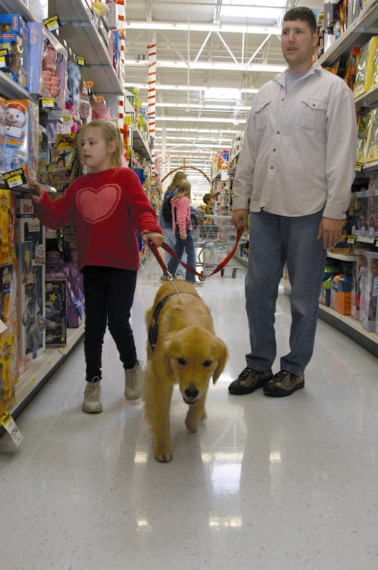 COLORADO SPRINGS, Colo. -- Jamie and her father, 1st Lt. Victor Rizzo walk through the toy aisle of a local department store with Berkley, a Canine Assistants service dog.  The Rizzos were awarded a service dog for 7-year-old Jamie, who is socially developed at a 2-year-old level. Canine Assistants trains golden retrievers and Labrador retrievers to assist people with physical and mental disabilities.  Lieutenant Rizzo is assigned to the 3rd Space Operations Squadron at nearby Schriever Air Force Base.  (U.S. Air Force photo by Senior Airman Mike Meares)