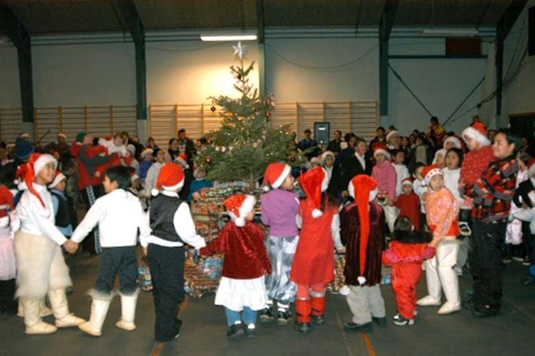 QAANAAQ, Greenland -- Children here dance around the Christmas tree just before opening gifts at the Julemand Celebration on Dec. 20.  The gifts were provided by the Airmen of Thule Air Base.  (U.S. Air Force photo by 1st Lt. Jennifer Tribble)