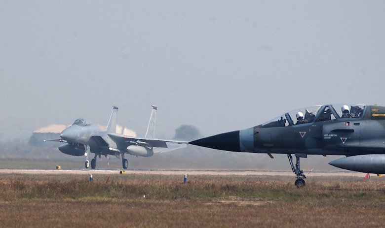 GWALIOR AIR FORCE STATION, India (AFPN) -- As an Indian air force M-2000 Mirage waits to taxi to the runway, a U.S. Air Force F-15 Eagle takes off.  Both American and Indian air forces are participating in Cope India 04, a bilateral dissimilar air combat exercise.  (U.S. Air Force photo by Tech. Sgt. Keith Brown)