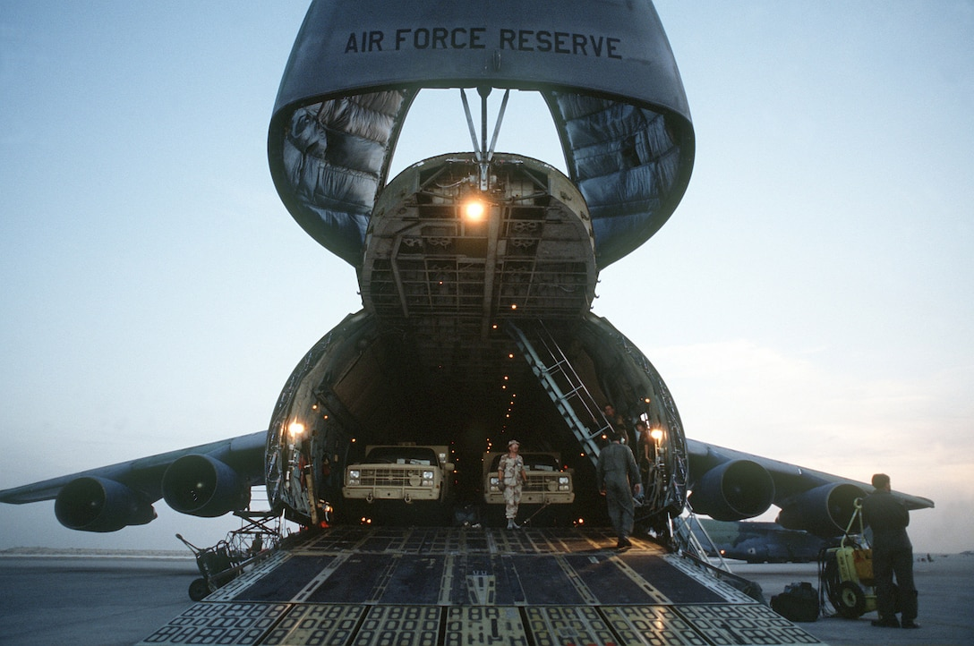 Military trucks are unloaded from the nose ramp of a C-5A Galaxy transport aircraft of the U.S. Air Force Reserve, Military Airlift Command, in support of Operation Desert Shield. (U.S. Air Force photo)