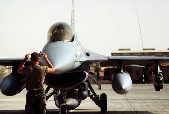 1990's -- A ground crewman guides a 388th Tactical Fighter Wing F-16C Fighting Falcon aircraft onto the taxiway.  The 388th TFW is deploying to Saudi Arabia to take part in Operation Desert Shield.  Mounted on the aircraft's left outboard wing pylon is an AN/ALQ-131 Electronic CounterMeasures pod; mounted on the side of the engine intake is a Low Altitude Navigation, Targeting Infrared Night (LANTIRN) navigation pod.