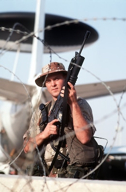 Airman 1st Class Robert Mott of the 90th Security Police Group stands guard near an E-3A Sentry aircraft during Operation Desert Shield.  Mott is armed with an M-16A1 rifle equipped with an M-203 grenade launcher.