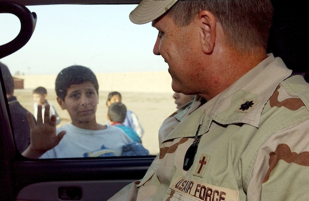SOUTHWEST ASIA (AFPN) -- An Iraqi boy waves goodbye to Chaplain (Lt. Col.) Steven Keith after he delivered clothing, food and other items donated by airmen at Baghdad International Airport, Iraq.  Chaplain Keith is assigned to the 447th Air Expeditionary Group.  (U.S. Air Force photo by Tech. Sgt. Lisa Zunzanyika)