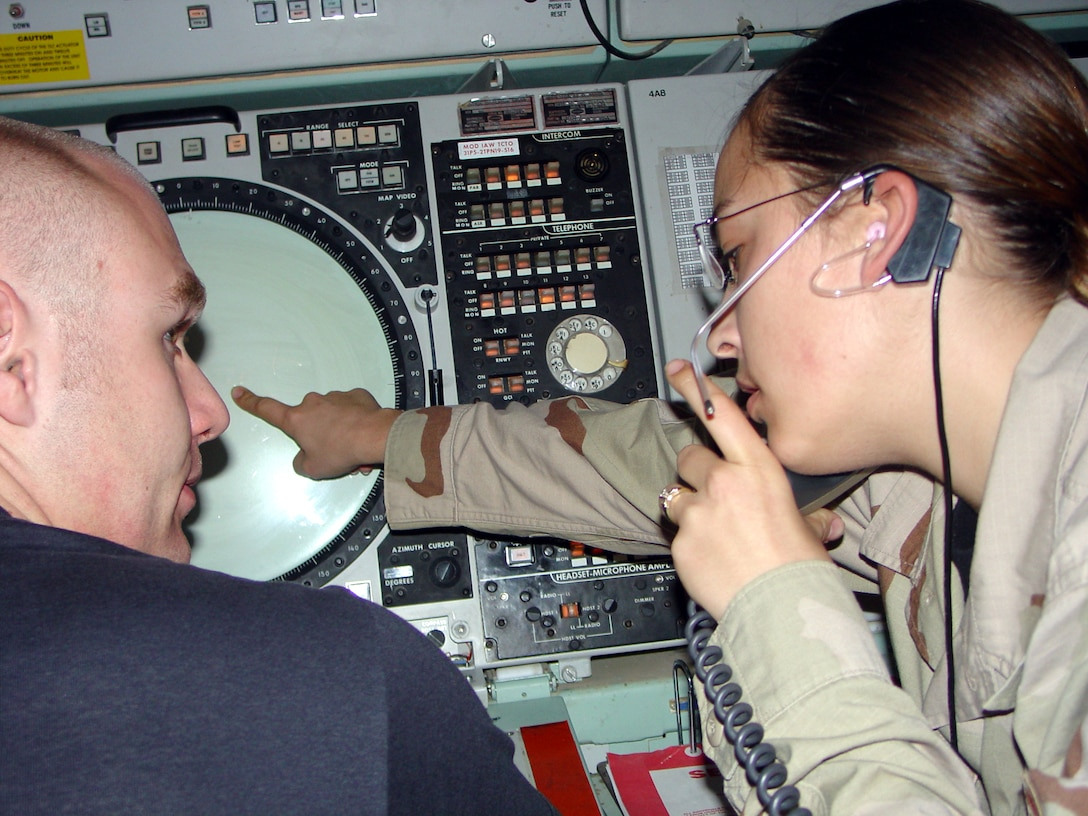 TALLIL AIR BASE, Iraq -- Senior Airman Caryn Baksis informs Senior Airman Jesse Fox of an aircraft entering the Tallil airspace that is being controlled by the Kuwaiti Center.  Airmen Baksis and Fox are 332nd Expeditionary Operations Support Squadron air traffic controllers.  Airman Baksis is deployed from Cannon Air Force Base, N.M., and Airman Fox is deployed from Ellsworth AFB, S.D.  (U.S. Air Force photo by Staff Sgt. Chris Stagner)