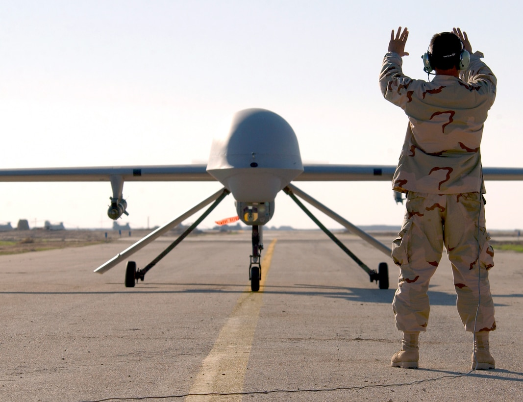 TALLIL AIR BASE, Iraq -- Senior Airman Robert Mascorro marshals an RQ-1 Predator aircraft here Jan. 20.  The Predator is a remotely piloted vehicle that provides real-time surveillance imagery supporting Operation Iraqi Freedom.  Airman Mascorro is assigned to the 46th Expeditionary Reconnaissance Squadron.  (U.S. Air Force photo by Staff Sgt. Suzanne M. Jenkins)