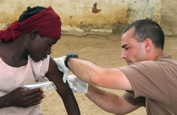 CAMP LOUMIA, Chad -- Staff Sgt. Rick English immunizes a Chadian girl while on a humanitarian mission here.  He is a medical technician with the 439th Aerospace Medical Squadron at Westover Air Reserve Base, Mass.  The medical team saw more than 2,800 patients from 16 villages during the 15-day mission.  (U.S. Air Force photo by Tech. Sgt. Chance Babin)