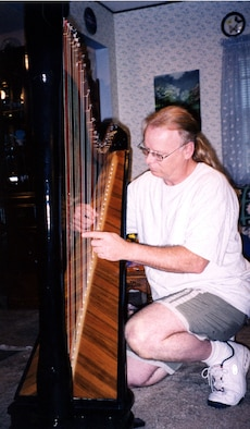 LONG BEACH, Miss. -- Fred McMichael plays the harp that took him three years to make at his home here.  He is a local network administrator at nearby Keesler Air Force Base.  (U.S. Air Force photo by Susan Griggs)