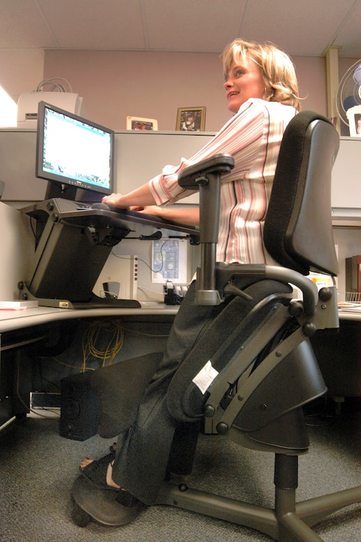 ROBINS AIR FORCE BASE, Ga. -- Melanie McDonald, a speech writer with the commander's action group here, uses a specially designed hydraulic chair and desk elevation system to help alleviate her back pain.  (U.S. Air Force photo by Sue Sapp)