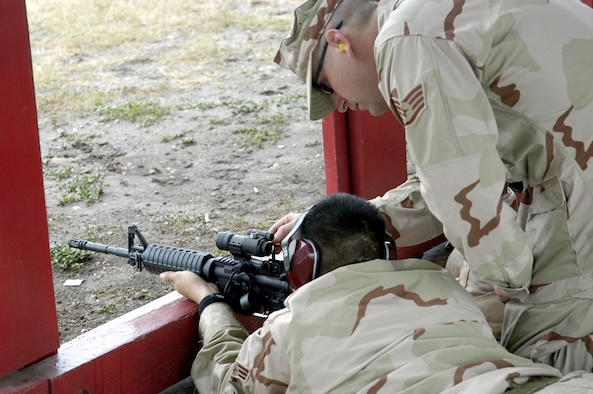 "LACKLAND AIR FORCE BASE, Texas -- Staff Sgt. Scott Grant (right) teaches Senior Airman Jeffery Salonga to use an M-4 carbine during a Basic Combat Convoy Course here.  Sergeant Grant was helping students sight in the ""red dot"" aiming optics of their new rifles.  He is a course instructor and is assigned to the 342nd Training Squadron.  (U.S. Air Force photo by James Coburn)"