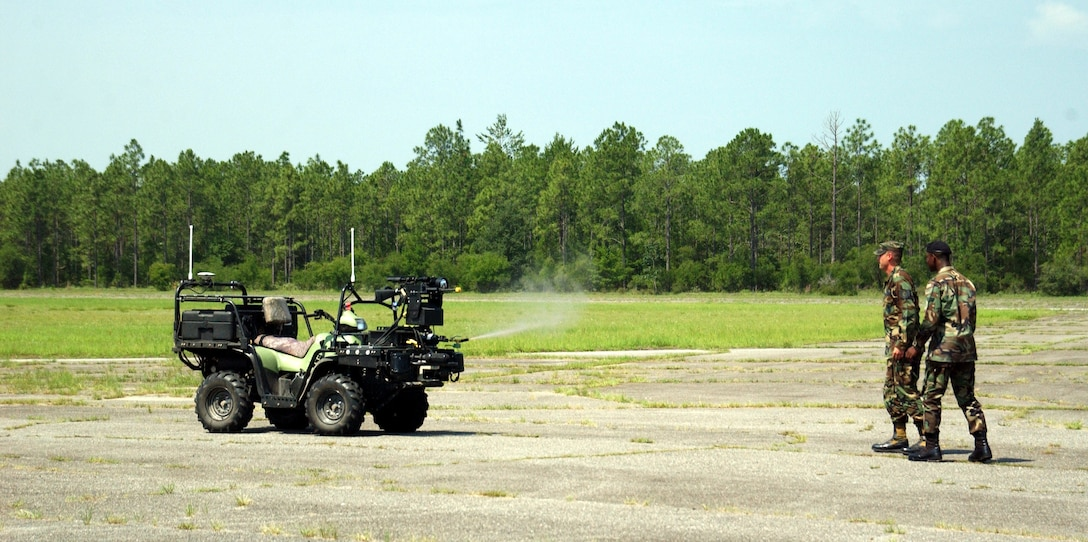 EGLIN AIR FORCE BASE, Fla. -- Troops stand back as the Scout robotic vehicle fires pepper spray during a demonstration June 22.  The robot is also armed with an M-16A2 rifle which is controlled from a remote location.  (U.S. Air Force photo by Gary Emery)