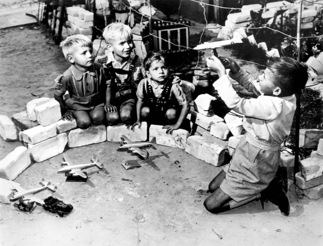 """""""OPERATION VITTLES"""" (Berlin Airlift) -- Berlin youngsters who live near the Tempelhof Air Force Base, where the U.S. Air Force transport planes unload their airlift supplies, play at a game called """"Luftbrucke"""" (air bridge).  They use model American planes which are sold in German toy shops throughout the western sector of Berlin. (U.S. Air Force photo)"""
