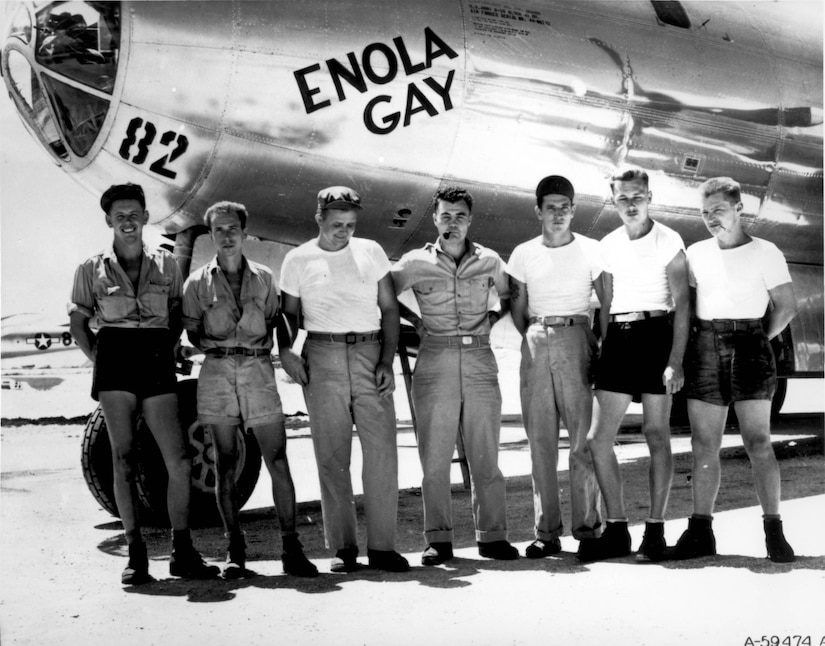 Seven men stand in front of the nose of a B-29 bomber.