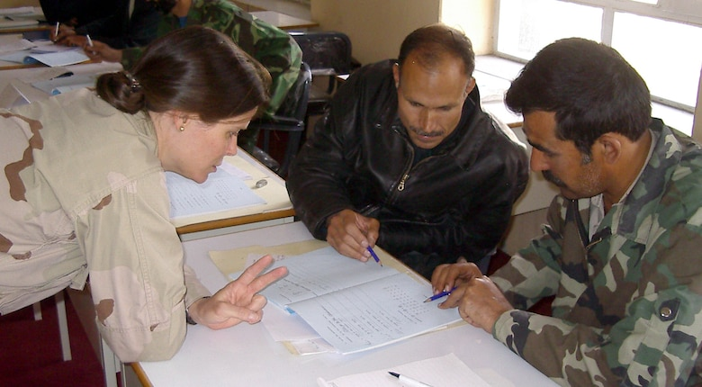 KABUL, Afghanistan -- Maj. Susan Washington helps Afghan air force pilots, Col. Abdul Zaher (left) and Capt. Hafizullah, with their English.  She teaches a basic-English class to 10 Afghan air force senior pilots.  (U.S. Air Force photo by Maj. Richard C. Sater)