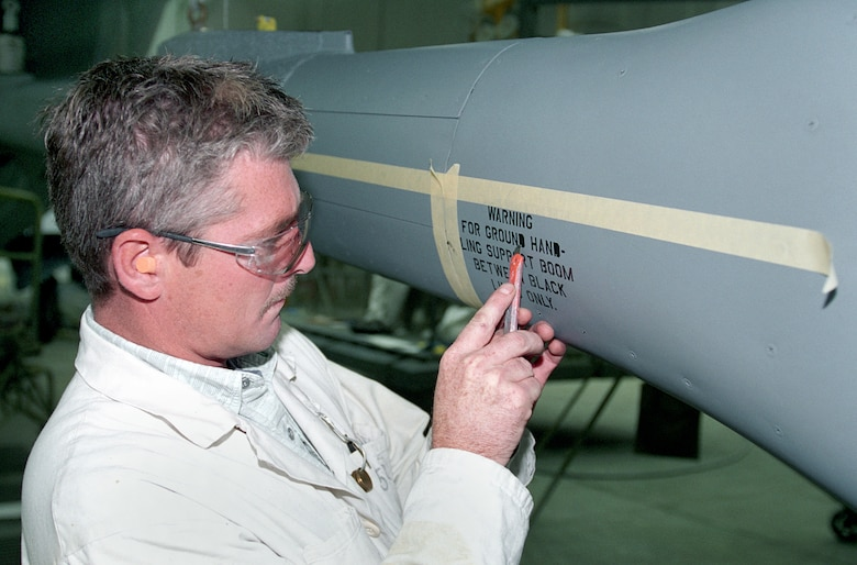 TINKER AIR FORCE BASE, Okla. -- Painter Steve Hamilton finishes stenciling on a KC-135 Stratotanker boom.  (U.S. Air Force photo by Margo Wright)