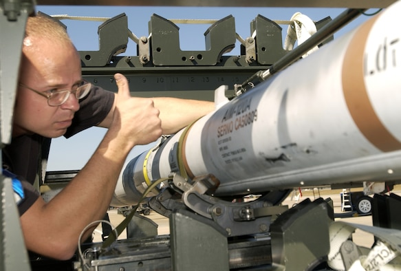TYNDALL AIR FORCE BASE, Fla. -- Staff Sgt. Kevin Skaggs prepares to load a missile during William Tell 2004 here Nov. 8.  This is the 50th anniversary of the competition, which tests an aircrew's ability to perform under combat conditions.  Two weeks of competition will challenge pilots, weapons loaders and maintainers from five F-15 Eagle fighter squadrons.  Sergeant Skaggs is assigned to the 95th Air Maintenance Unit here.  (U.S. Air Force photo by Staff Sgt. Tanika Bell)