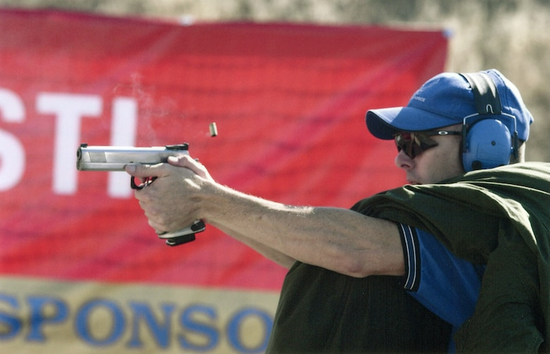 """OFFUTT AIR FORCE BASE, Neb. -- Maj. Roger Sherman fires his weapon during the U.S. Practical Shooting Association National Championship in July 2003.  The shooting scenario required Major Sherman to hold a 40-pound """"friend"""" while simultaneously engaging targets.  He is assigned to U.S. Strategic Command's global operations directorate here.  (U.S. Air Force photo by Ray Solomon)"""