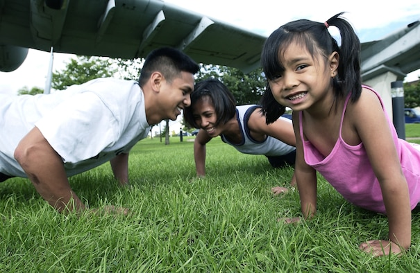 SPANGDAHLEM AIR BASE, Germany -- Staff Sgts. Rodolfo (left) and Mary Anne Reyes have made working out a family affair.  Five-year-old Reanna shows her warrior spirit by doing push-ups with her mom during daily workouts at home.  (U.S. Air Force photo by Master Sgt. Keith Reed)