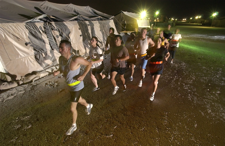 """AL UDEID AIR BASE, Qatar -- Airmen from the 379th Air Expeditionary Wing here participate in an evening """"fun run"""" to keep fit and escape the daytime heat.  Airmen worldwide are on a similar track in preparing for the new Air Force fitness test that replaces cycle ergometry with running, push-ups and sit-ups.  (U.S. Air Force photo by Master Sgt. Lance Cheung)"""