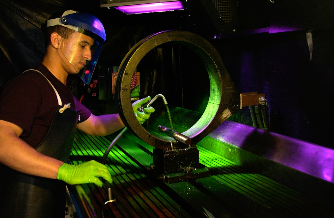 CHARLESTON AIR FORCE BASE, S.C. -- Airman 1st Class Kenny Payamps uses fluorescent magnetic particle testing to inspect a water separator bolt from a C-17 Globemaster here.  Airman Payamps is a non-destructive inspection testing journeyman assigned to the 437th Maintenance Squadron.  (U.S. Air Force photo by Tech. Sgt John M. Foster)