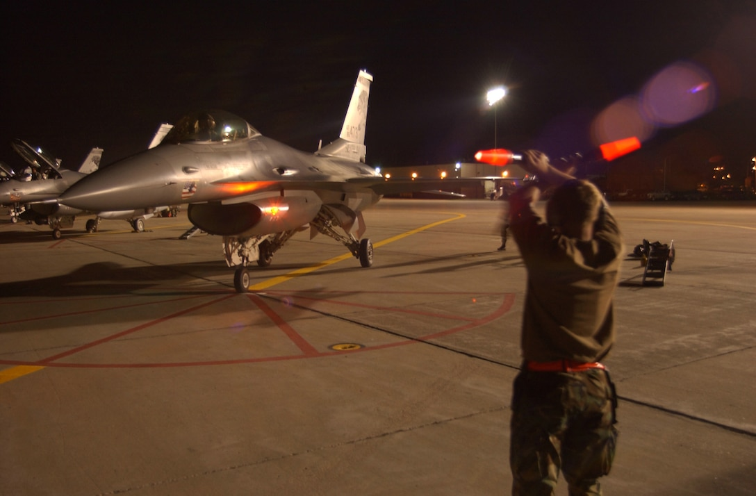 SIOUX FALLS, S.D. -- A crew chief guides an F-16C Fighting Falcon into place after completing a night sortie here Sept. 11.  The South Dakota Air National Guard's 114th Fighter Wing is conducting night flying missions during their September unit training assembly.  (U.S. Air Force photo by Staff Sgt. Mike Frye)